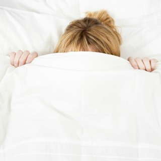 Young woman lying in bed doesn't want to wake up. Copy space